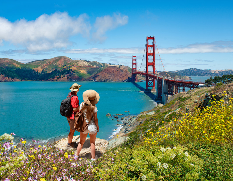 Couple looking at beautiful summer coastal landscape, on hiking
